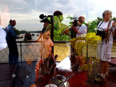 [image] Interview set with Thalassa on board the Bassac. In the reflection, the stage, with Laurent Bignolas and Benoit; through the window, Ánh, Capt' Quyền and Lise Blanchet, who all act in the shade to make this happen.